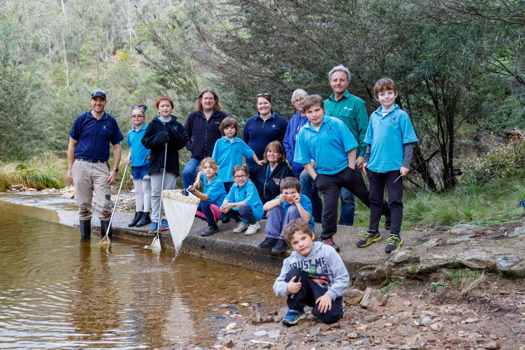 Members of the EGCMA, Greening Australia amd Bug Blitz stand alongside students of Clifton Creek Primary on the banks of the Nicholson River at Deptford.