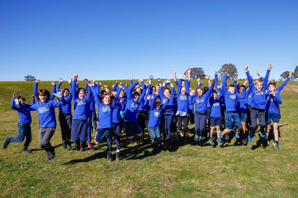 Students of Lindenow Primary jump for joy on a grassy hill near Skull Creek.