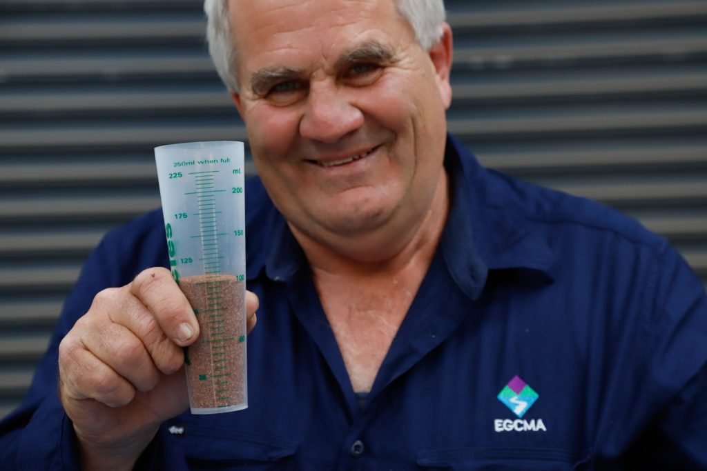 EGCMA Works Coordinator Peter Brookes holds a plastci container full of seed ready to be planted.